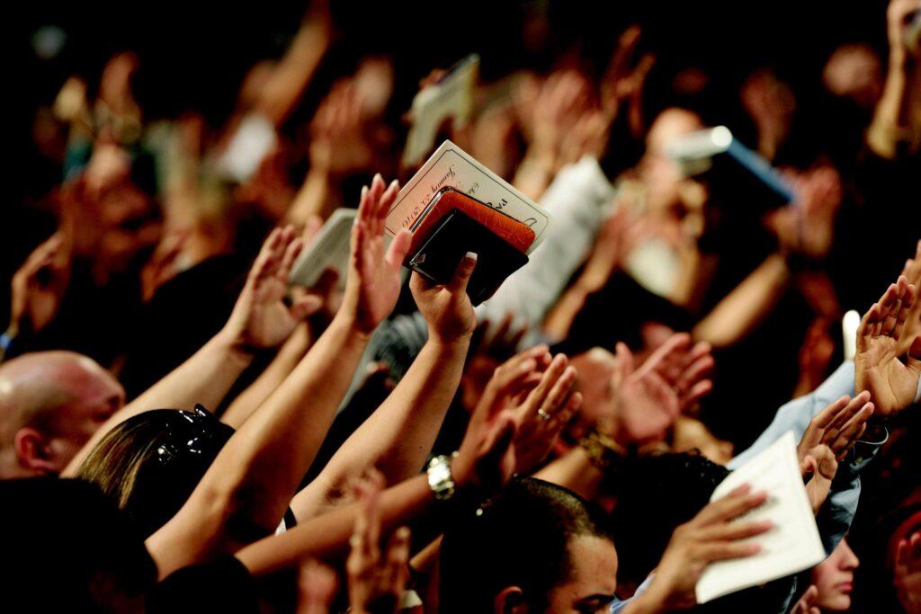 multitud de personas levantando sus manos sosteniendo biblias y panfletos