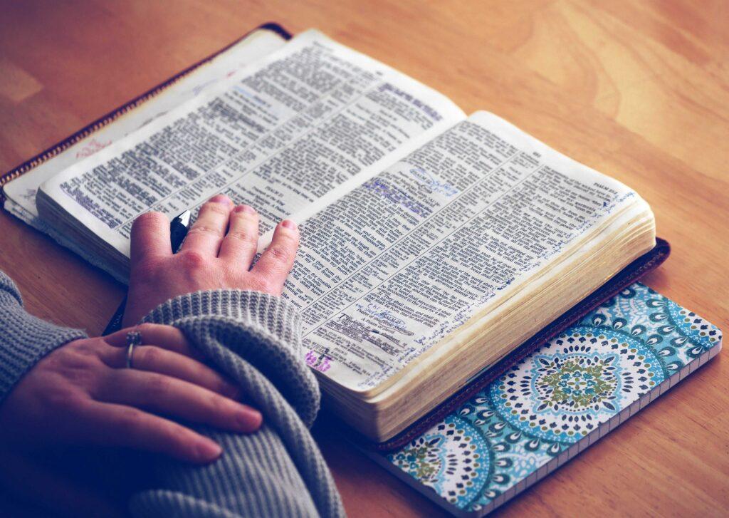 Manos de mujer con un bolígrafo para marcar la biblia