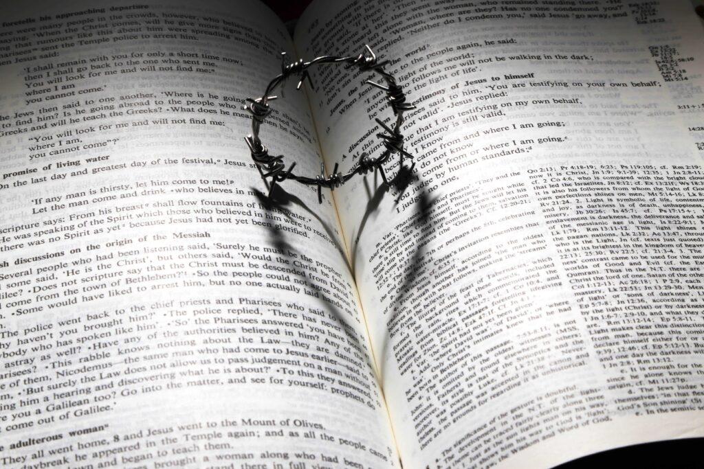 Aro de púas sobre una biblia dejando ver el contorno de un corazón con su sombra sobre la biblia