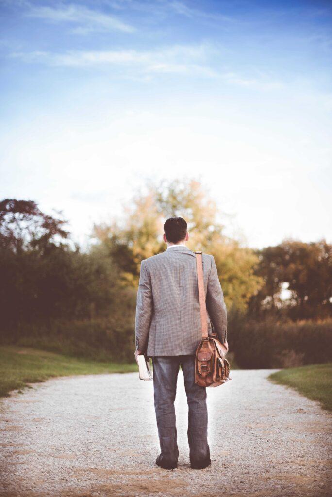 Hombre sosteniendo biblia frente a un camino