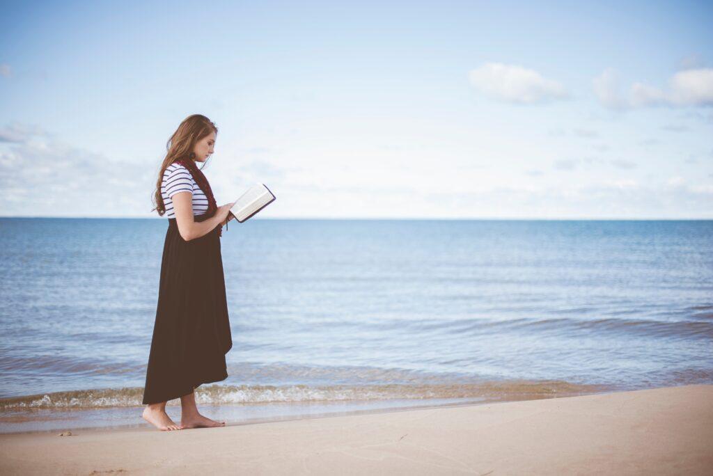 Mujer leyendo la biblia mientras camina sobre la arena en la playa