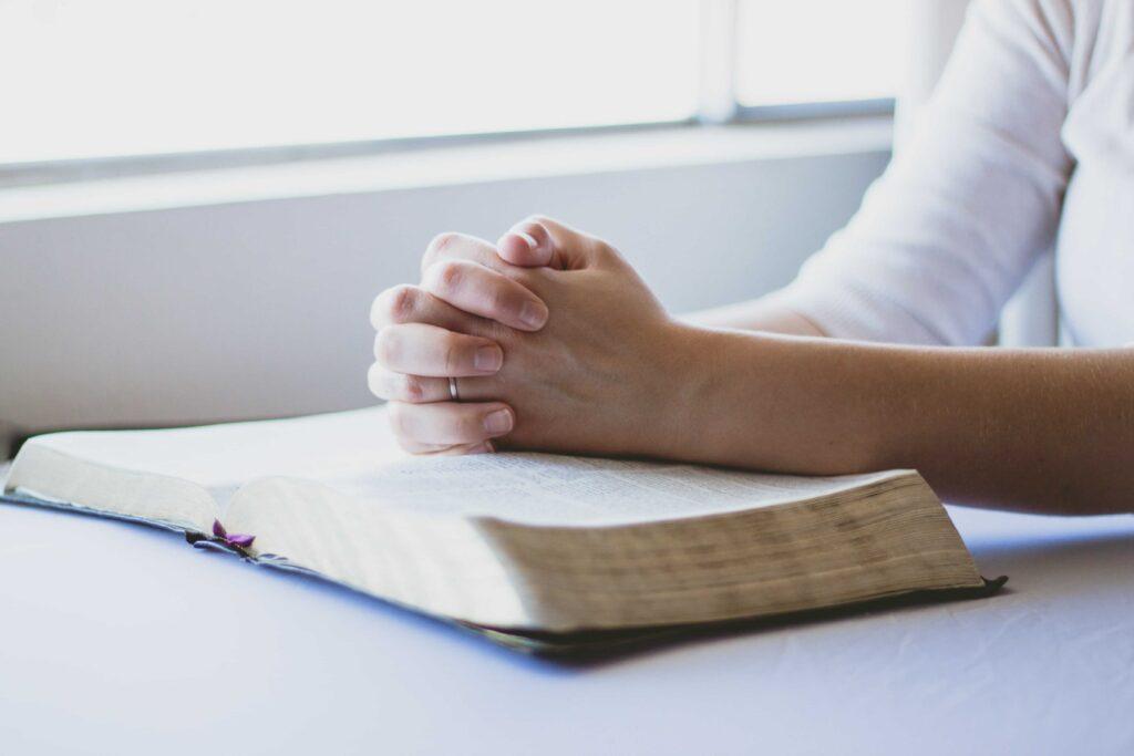 Manos rezando de una mujer sobre una biblia