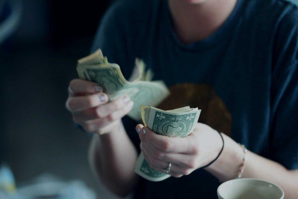 Mujer con dinero en mano para servicios de traducción