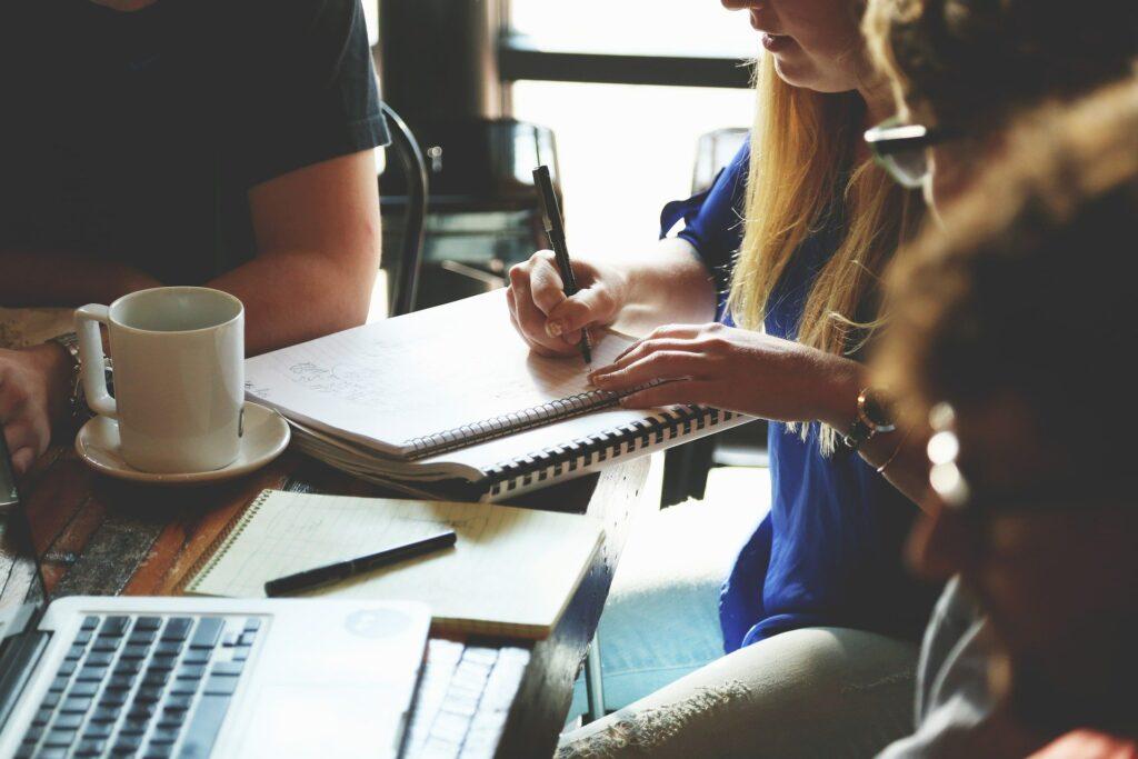 Reunión de varias personas en la que una de ellas escribe sobre en una libreta