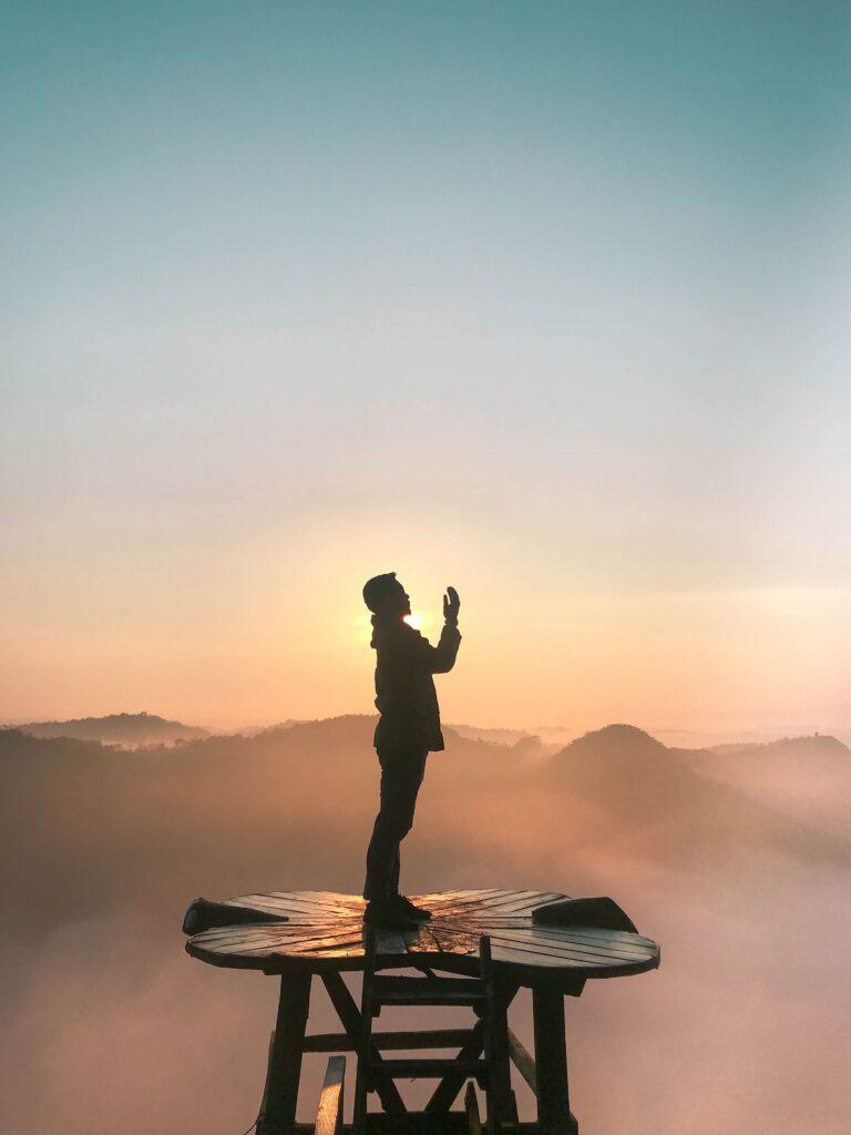 Contorno de hombre rezando con fondo de puesta del sol