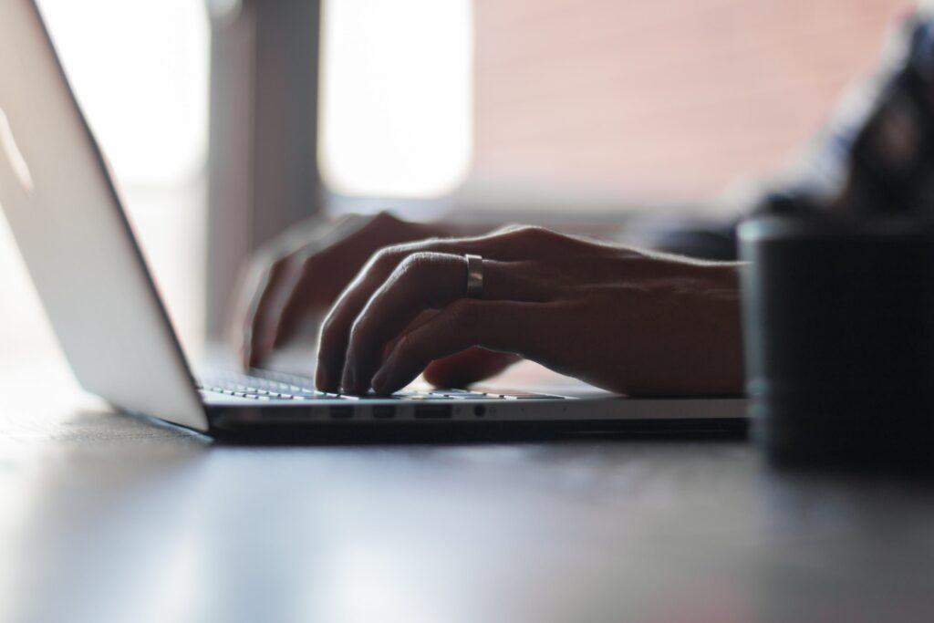 Manos de mujer escribiendo en una laptop