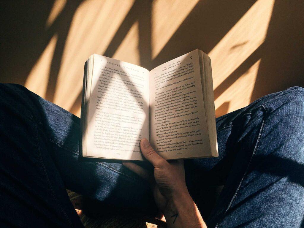 Persona sentada en el suelo leyendo un libro